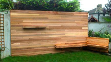A cement finished garden wall, made into a garden feature, using western red cedar cladding. The cement wall was battoned with pressure treated timber batons, and finished with western red cedar. A wrap around bench seat finishes the angle of the wall.