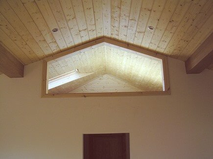 A ceiling finished in pine tongue and groove timber cladding. The cladding boards used for this were six by one tongue and groove, the edges of each board were etched with a router and sanded, to give a distinctive space between the tongue and groove boards.
