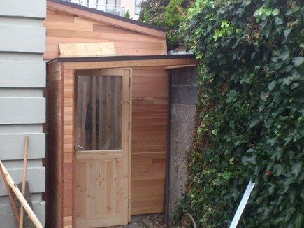 A timber frame garden room finished in red cedar cladding. The room is an extension off the side of a house, to be used as a utility room. There is access from the kitchen to this area. New doors were fitted, front and back, gaining access to both front and back gardens. The roof has been finished in clear polycarbonate sheeting, which lets in more light, this product also has insulation properties.