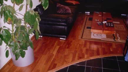 This is a semi solid cherry wood floor(engineered board), with a curved solid cherry wood border. This style of floor is also known as a floating floor. The flooring boards are glued together and rest on the foam underlay. Skirting board or trim can be used to finish this floor