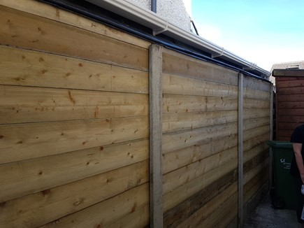 This lean to shed uses standard concrete fence posts and gravel boards as normal between neighbors, except the light panels have been replaced with 6 x 2 treated timber, as added security. This also finishes the divide very neatly for both parties.