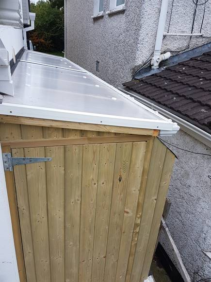 This roof is made up with 10mm polycarbonate twin wall sheeting.  This is a great product for this style of shed.  The polycarbonate sheeting is strong, clear and uv protected.  Along with the sheeting, many accessories are available to hold the roofing material firmly in place whilst remaining very tidy. The side passage shed in the image displays the F profile for the edges of the roof, the aluminum joiner bar between joining sheets. Wall flashing, Gutters and down pipe are also fitted.