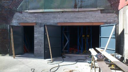 This solid concrete block wall is nine inches wide,built to close-in the arch, creating a storage unit. Two opening have been left, a single doorway and a double doorway. Both openings use rsj's(reinforced steel joists) to support the wall above. Steel security doors were then fitted to complete this secure storage solution.
