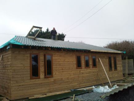 A timber frame home being wrapped in shiplap timber cladding