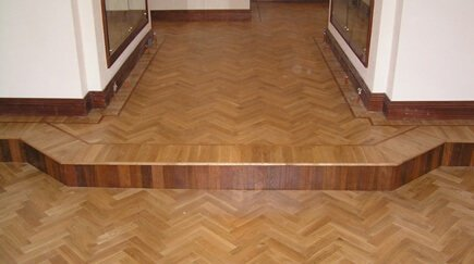 Flooring style, solid oak parquet floor with a herringbone design and a mahogany strip border. Oak and Mahogany woodblock were used to create this floor. The floor is mainly oak, with a mahogany strip creating a border and mahogany block finishing the risers on each step, Mahogany skirting board finishes the design. A Flooring adhesive was used with this floor.