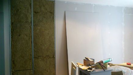 sound proof wall being constructed. The make-up consists of a metal stud wall, packed tight with insulation. Then a layer of plasterboard with all seams completely sealed with an acoustical sealant. Ceiling, floor, adjoining walls and any intermediate joints, all need acoustical sealant the full width of the joint.